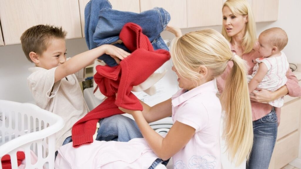 sibling fighting over laundry with disapproving mom