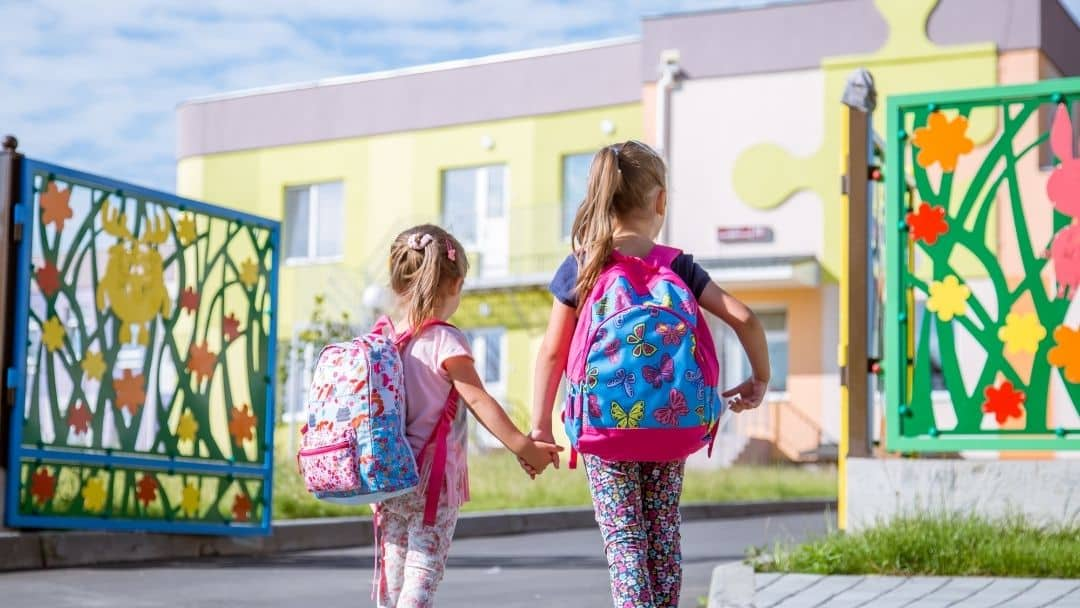 sisters walking into school with backpacks