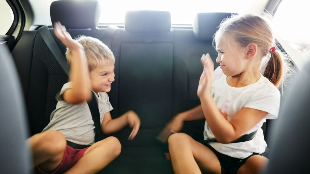 siblings fighting in the car with raised hands ready to hit