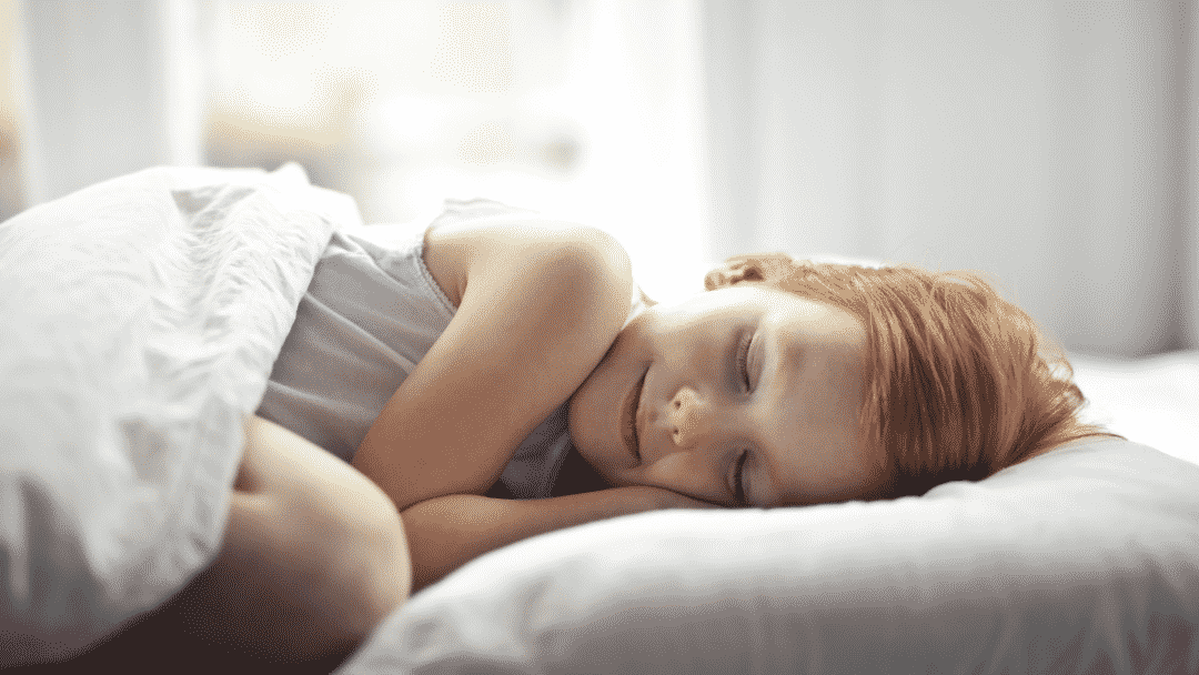 redheaded little girl resting happily in bed