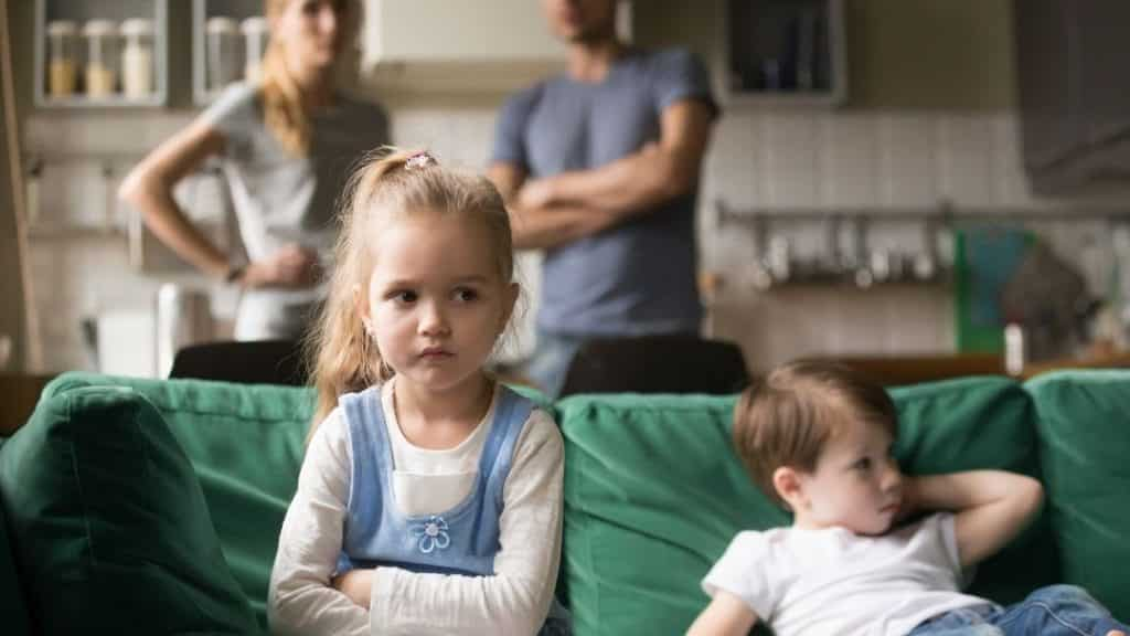 kids fighting all the time on a green couch - annoyed little blond girl and worried parents