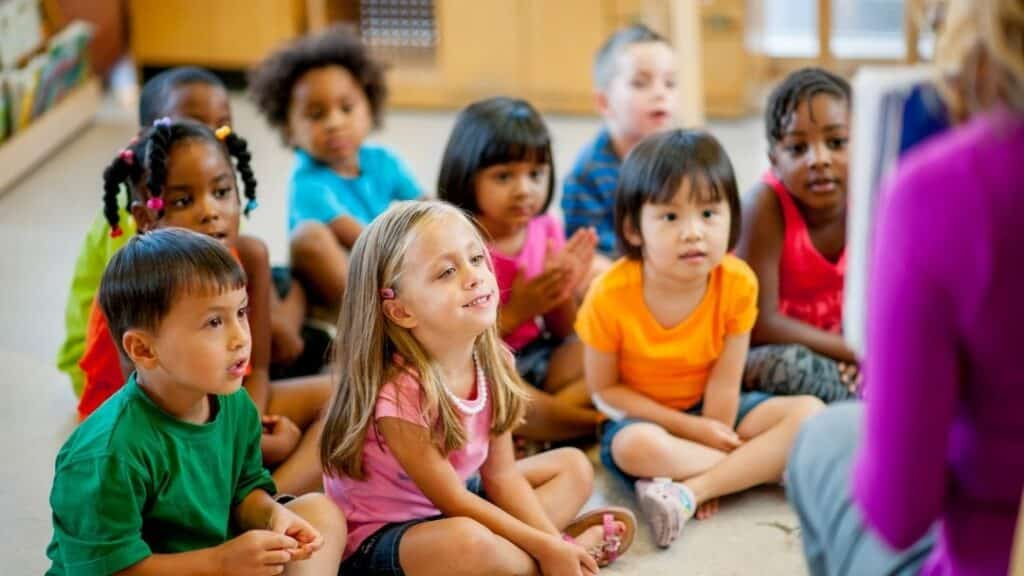 classroom full of students sitting at the rug, listening to the teacher