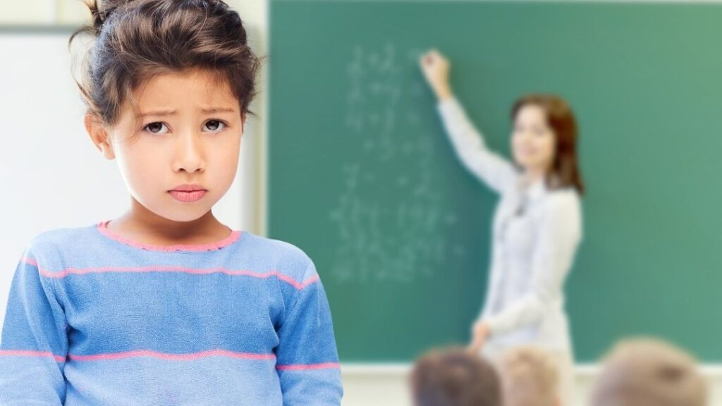 sad little girl in trouble at school with teacher in background