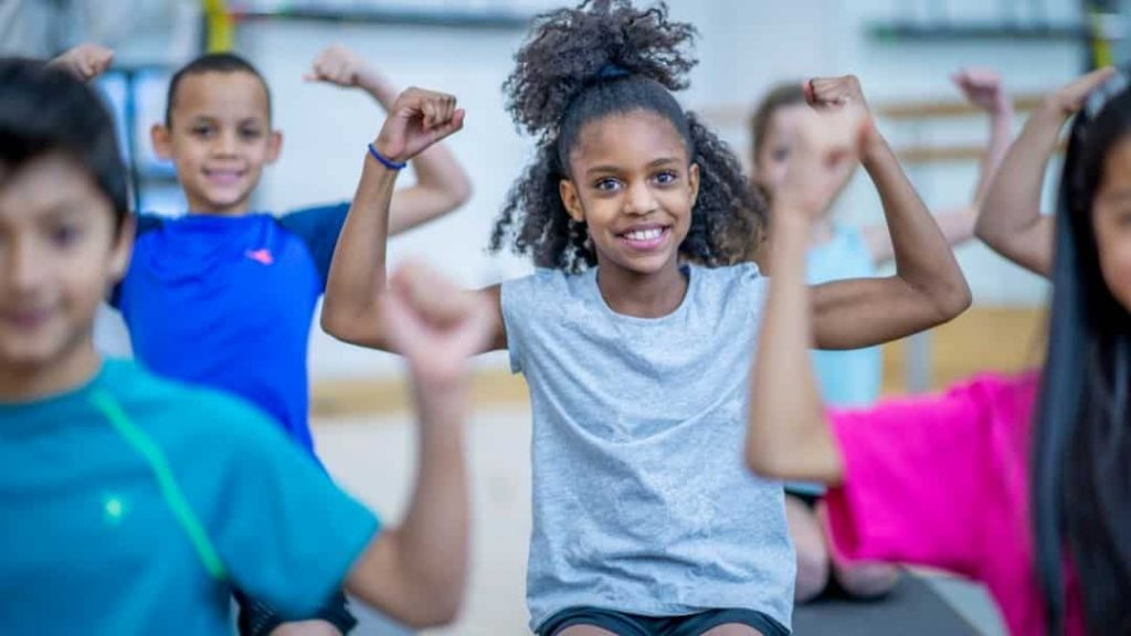 group of kids showing off their muscles in PE class