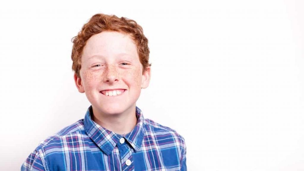 red headed, freckled boy smiling at the camera on a white background