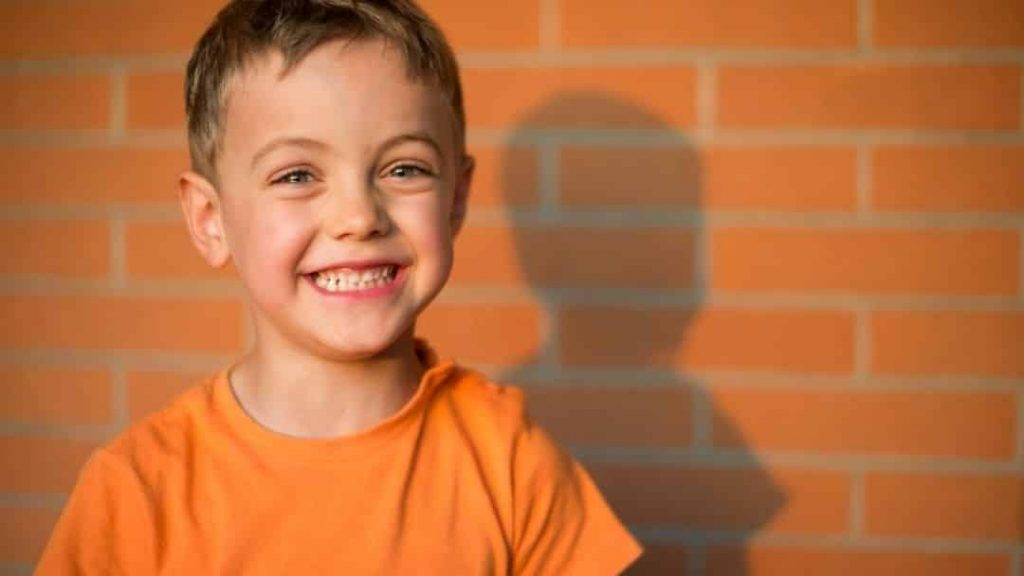 smiling little boy in front of a brick wall