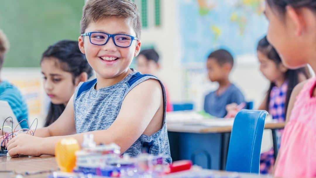 positive affirmations for kids - little boy smiling in class with glasses on