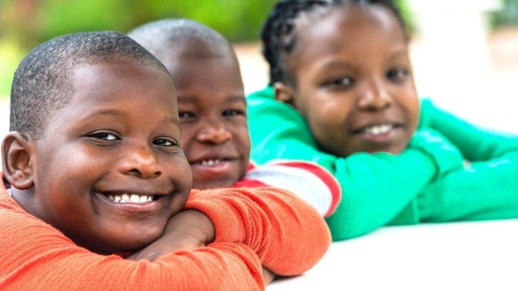 3 smiling kids sitting in class together - practicing positive affirmations for kids