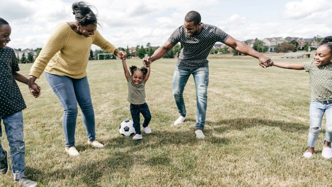 family playing soccer together outside