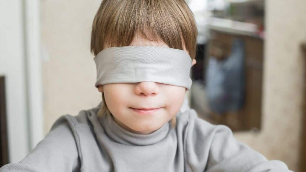 child with a blindfold on his eyes awaiting his mystery staycation