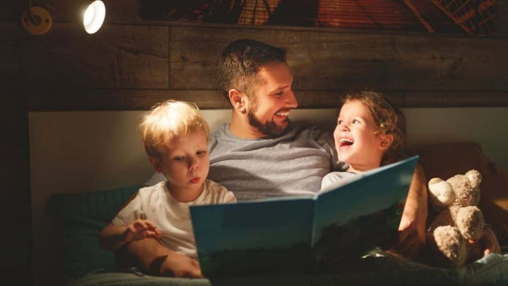 father reading to two small kids during their spring break staycation