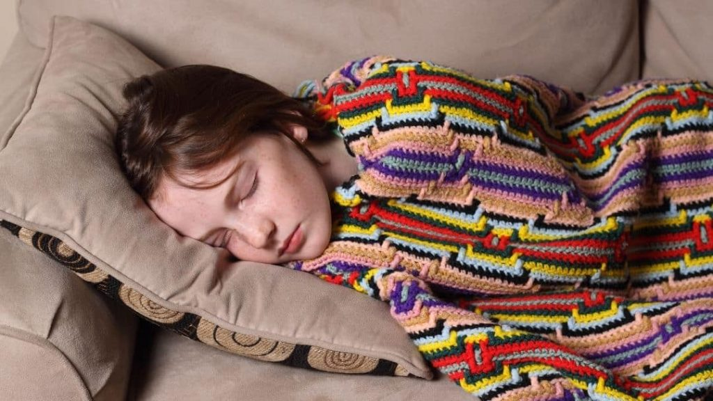 child taking a nap wrapped in a blanket on the couch during her spring break staycation