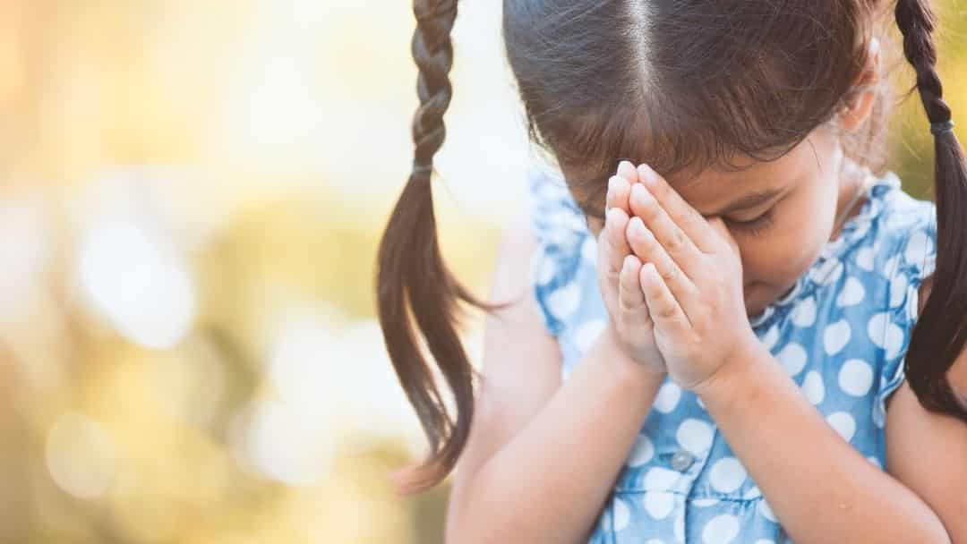 little girl with pigtails praying