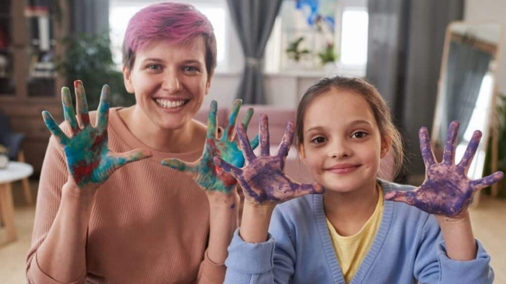 mother and daughter smiling with paint all over their hands