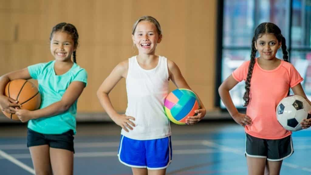 three little multicultural girls, each holding a different kind of ball and smiling