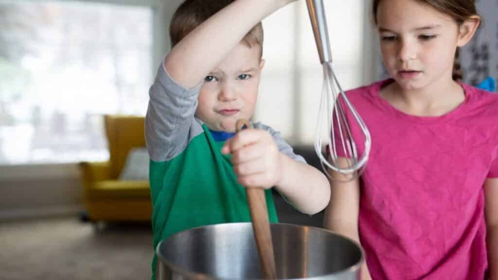 sister and brother cooking together and holding a whisk