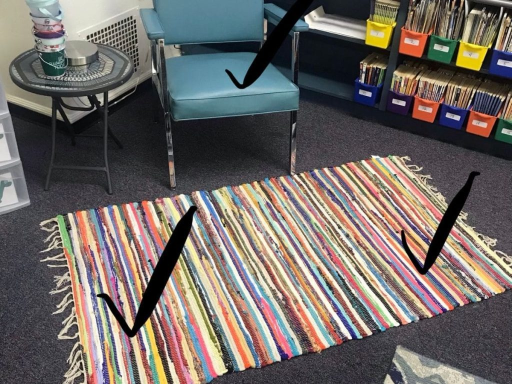 A picture of a rug and chair marked up with check marks to show where kids can sit.