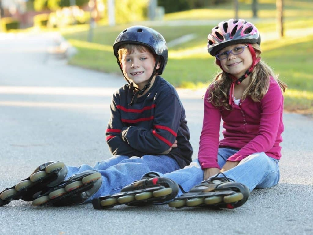2 kids sitting on the pavement rollerblades on
