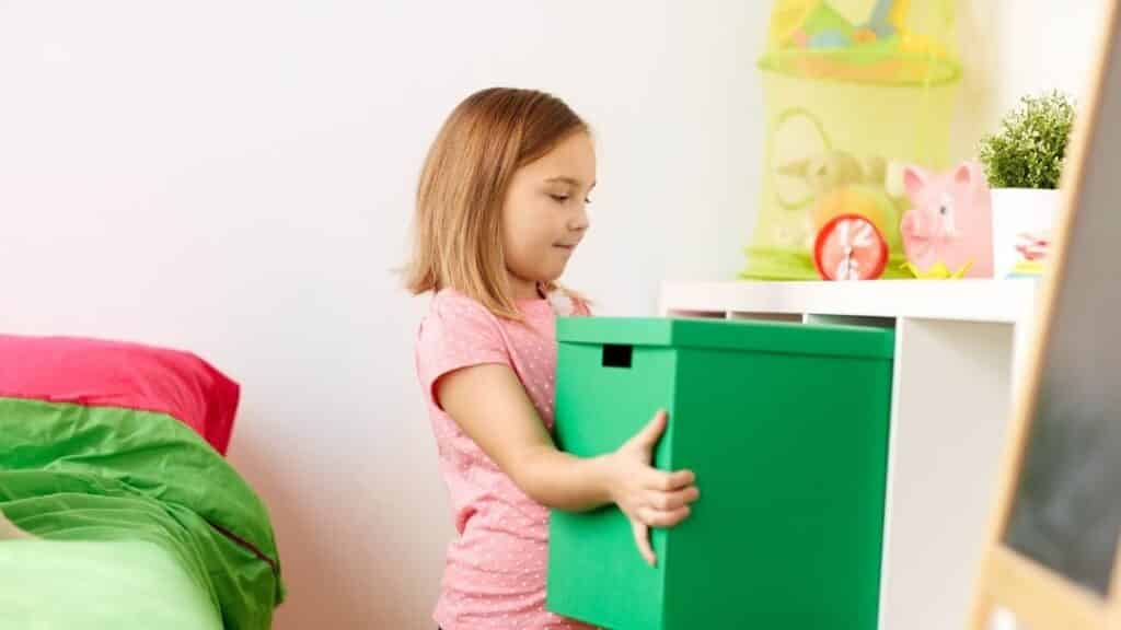 little girl pulling out fabric toy bins
