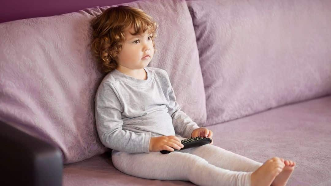little girl watching tv on a lavender couch