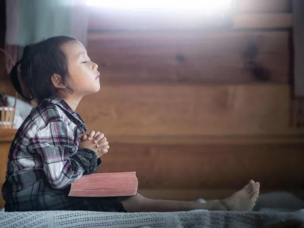 little girl praying with Bible in her lap