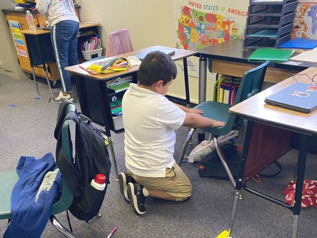 kid doing a classroom clean up wiping down his chair