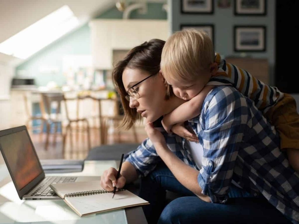 mom working on a plan with a pencil and child hugging her