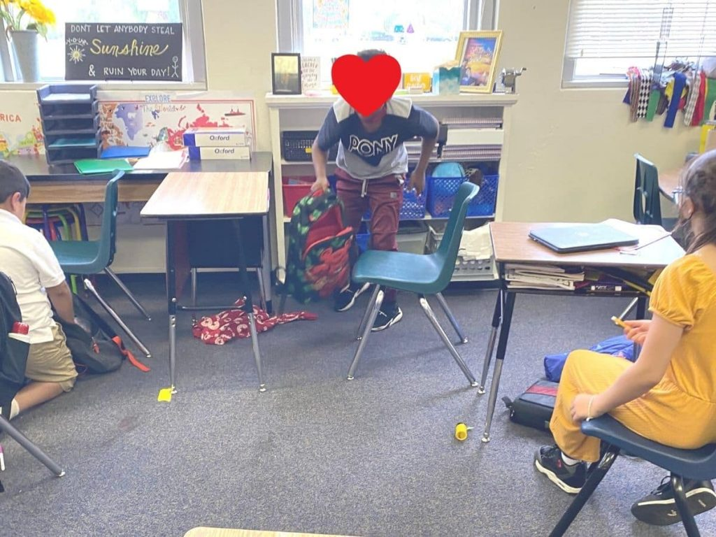 child cleaning up the classroom - seems in a hurry