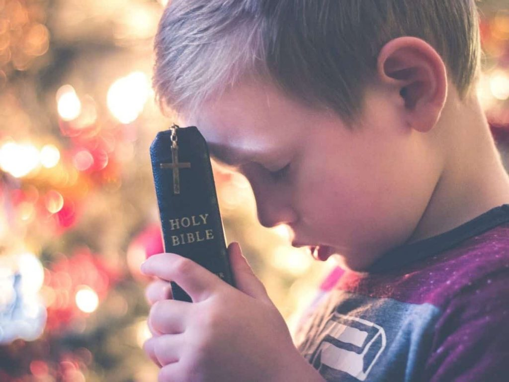 little boy with his forehead pressed against a Bible - how to explain the Trinity to a child