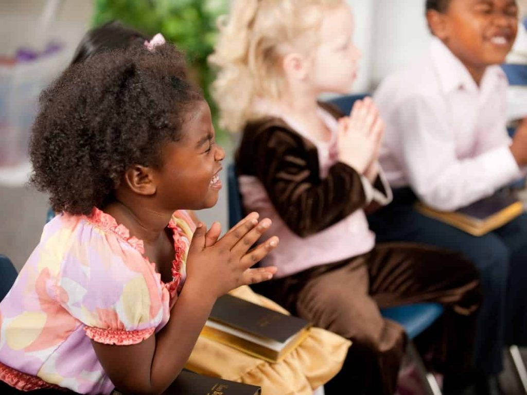 little kids praying at church with Bibles on their laps