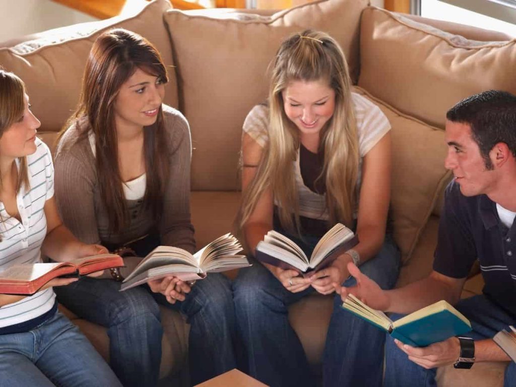 group of teenagers at Bible study on a couch studying the Trinity