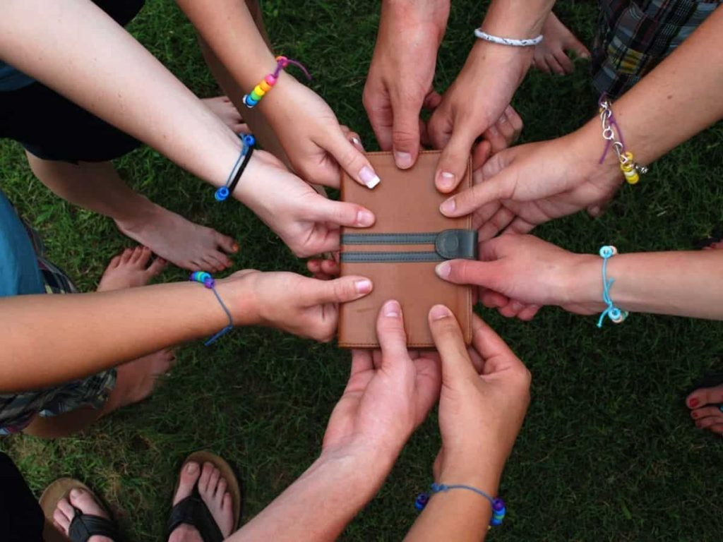 group of teenagers standing a circle, holding a shared Bible in the middle