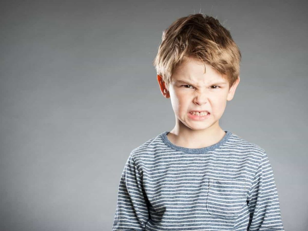 little boy with angry face - parents often give repeated, hollow threats