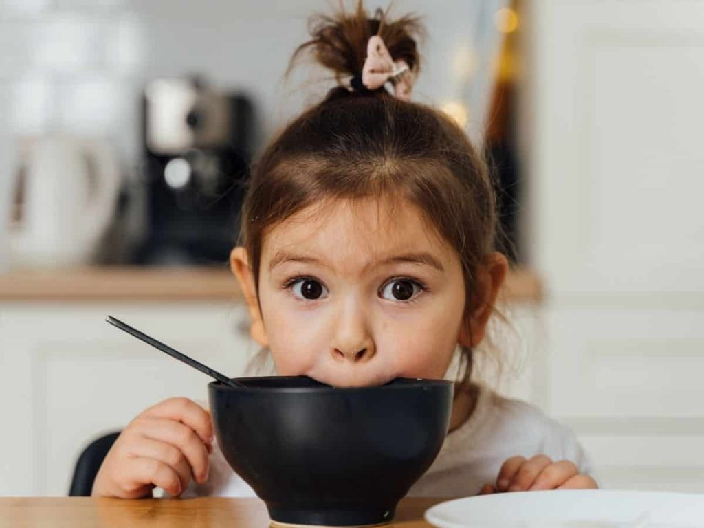little girl with her mouth on her bowl using bad manners at the dinner table, despite multiple threats
