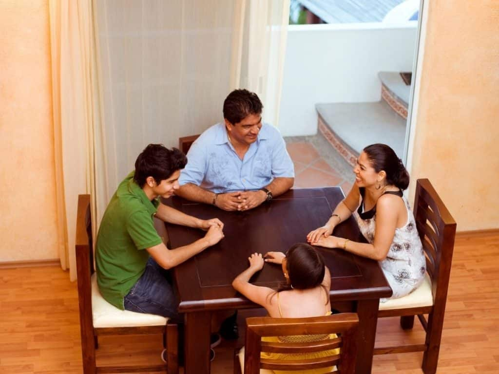 planning family of four at the dinner table for a summer block schedule for kids