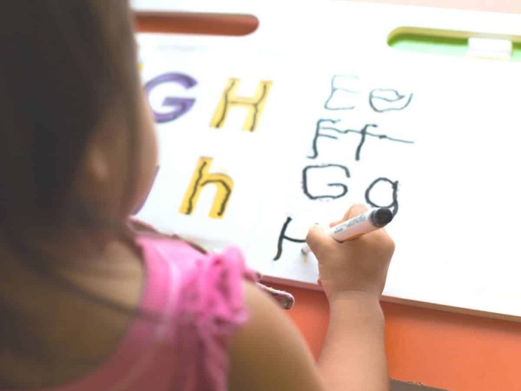little girl practicing tracing her letters so she doesn't write letters backwards