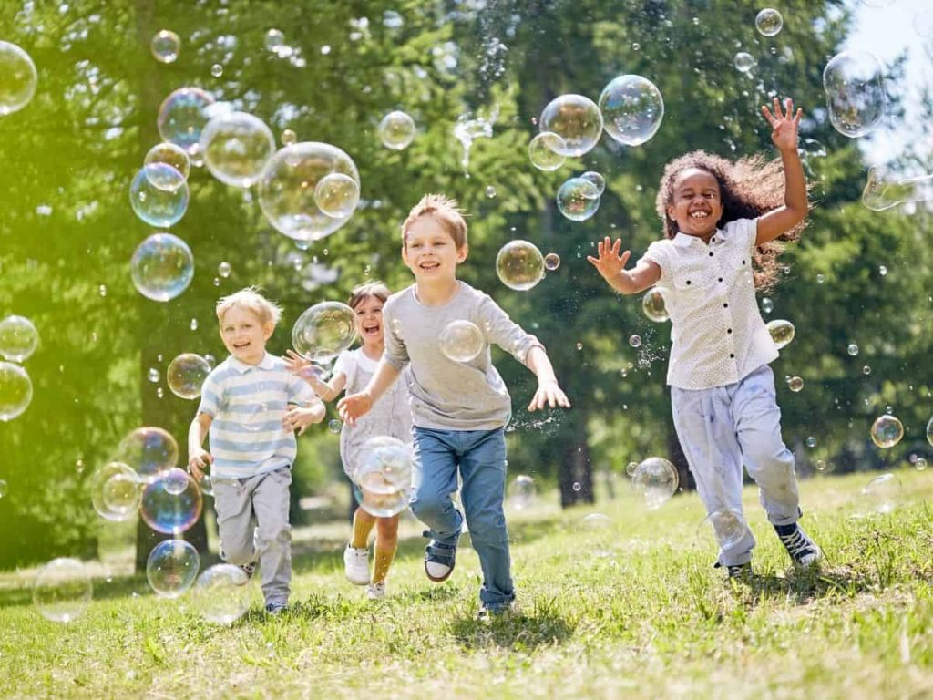 outside time for summer block schedule - bubble blowing group of kids