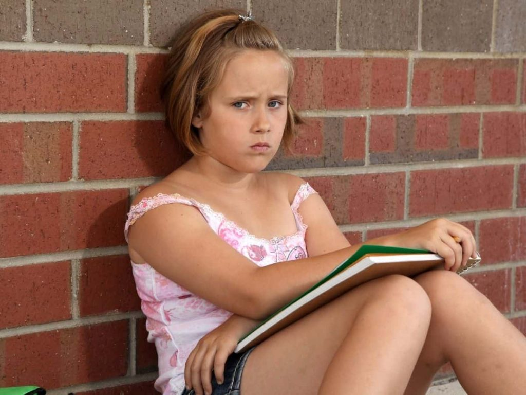 frowning girl with notebook in her lap leaning against brick wall