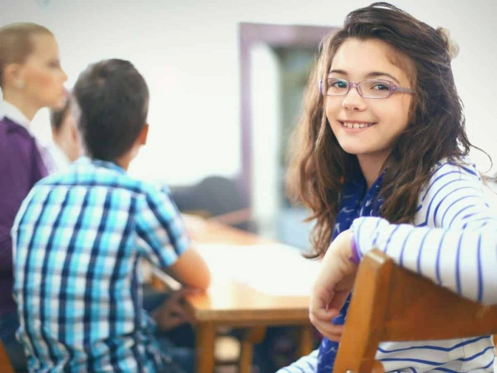 child talks too much in class - smiling at camera