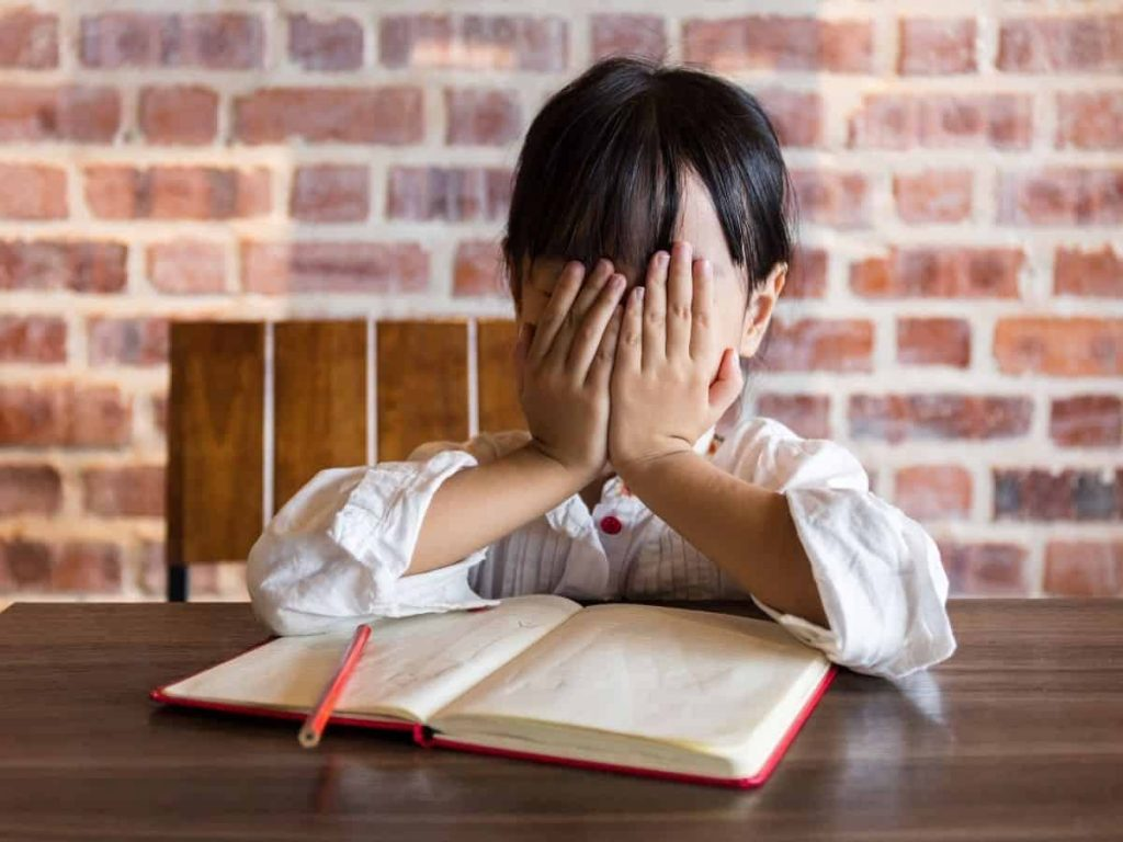 child falling behind in school - little girl with notebook and hands over face