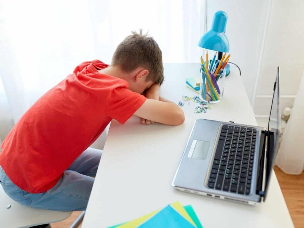 boy at his home desk with his head on his desk - frustrated that he's falling behind in school