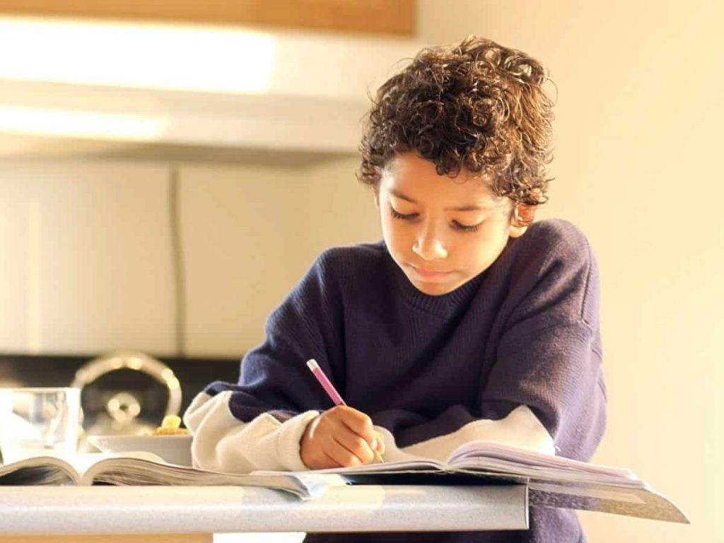 little boy working on his homework in a marbled planner