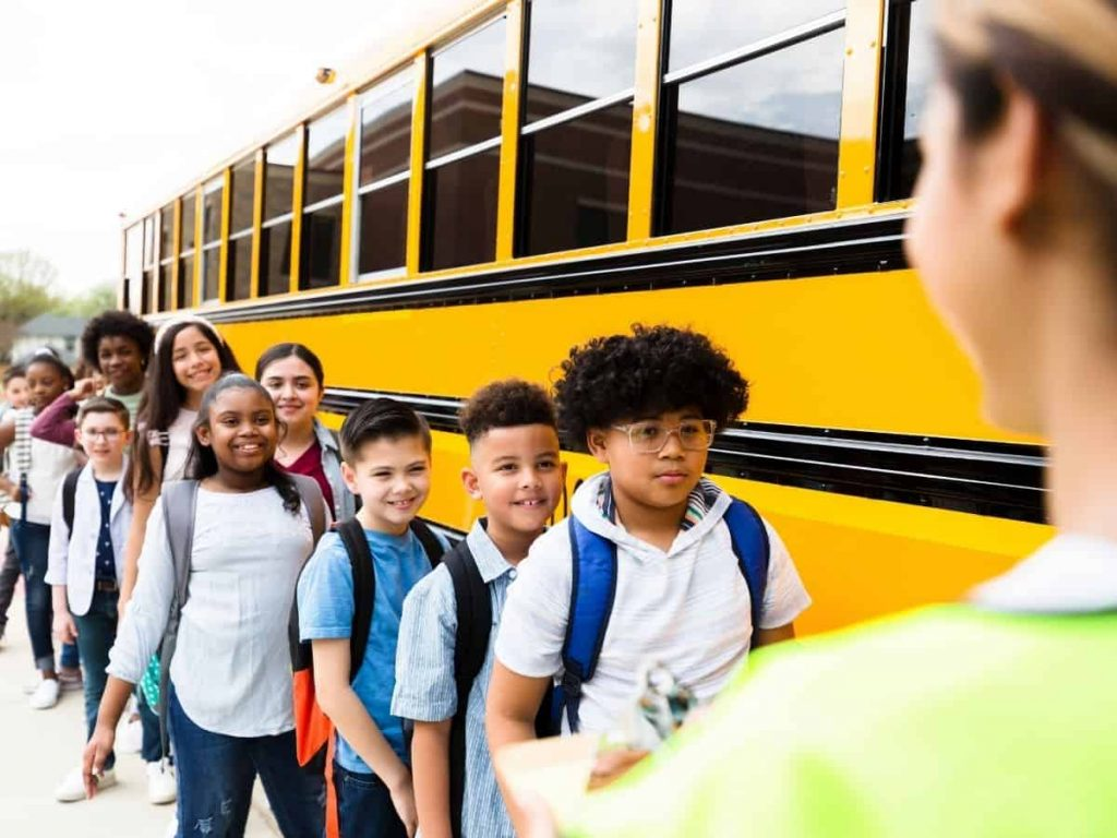 happy students waiting for the school bus