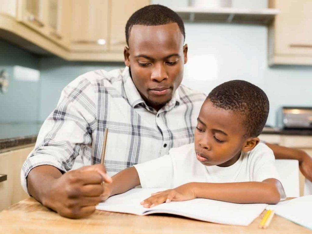 father and son practicing writing skills in a composition book