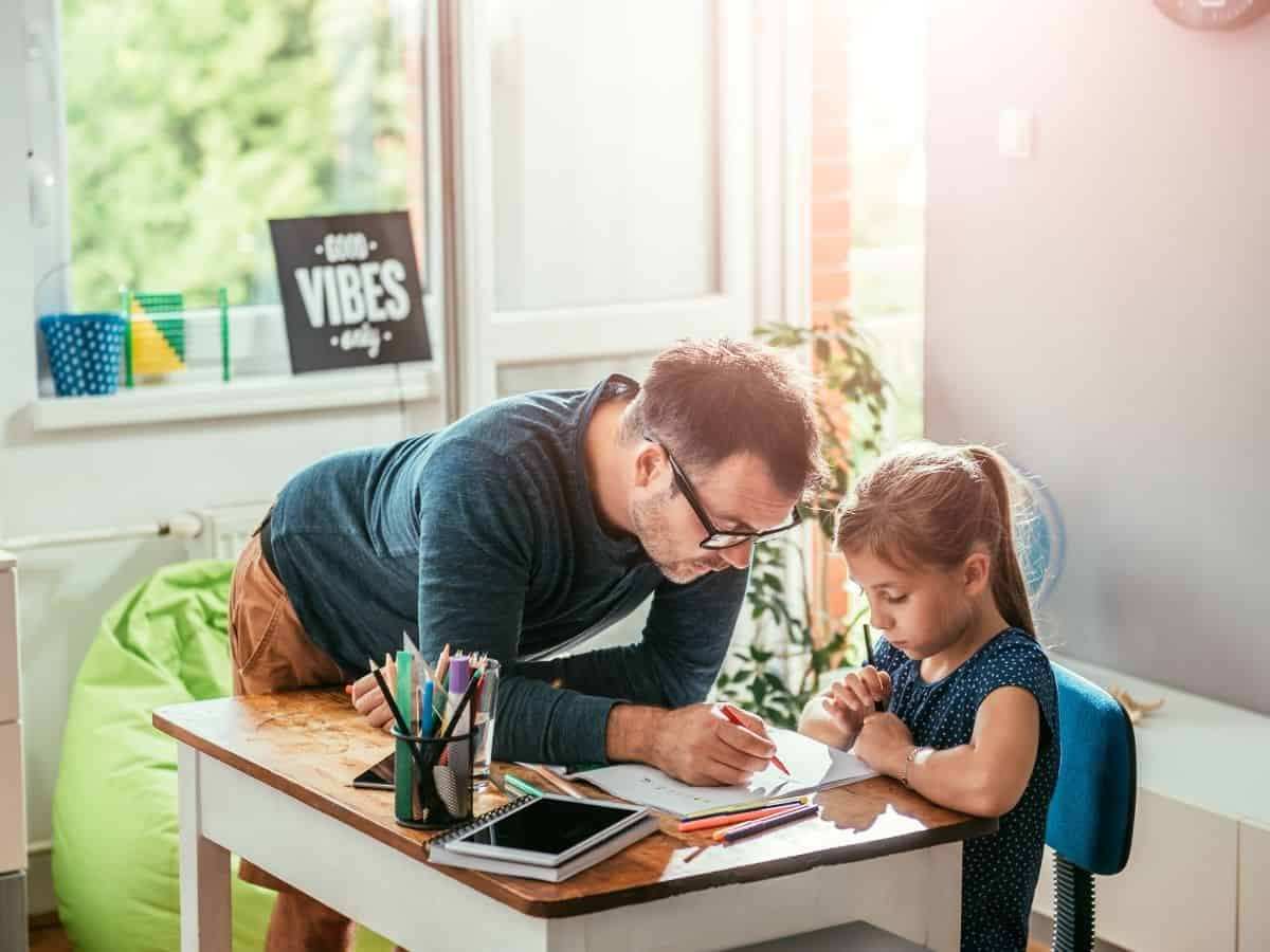 father and daughter doing homework together in the kitchen because child is falling behind in school