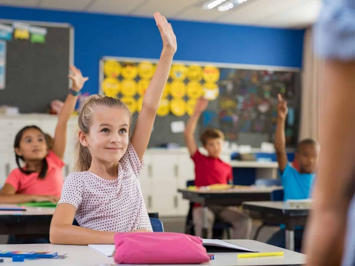 help your child succeed in school - little girl with hand raised in classroom