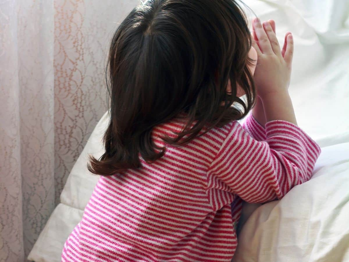 little girl in striped shirt praying at bedside