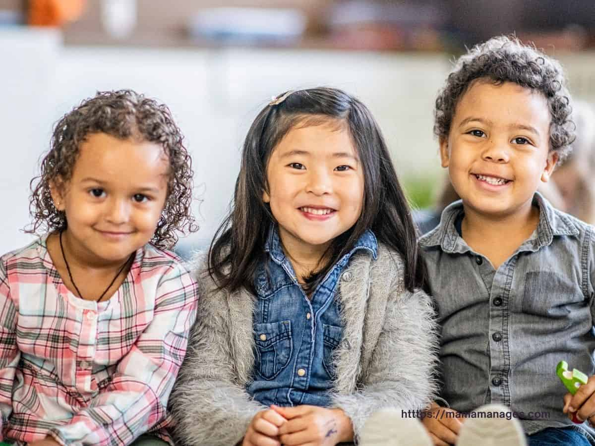 three little kids smiling in a row, excited about their classroom jobs