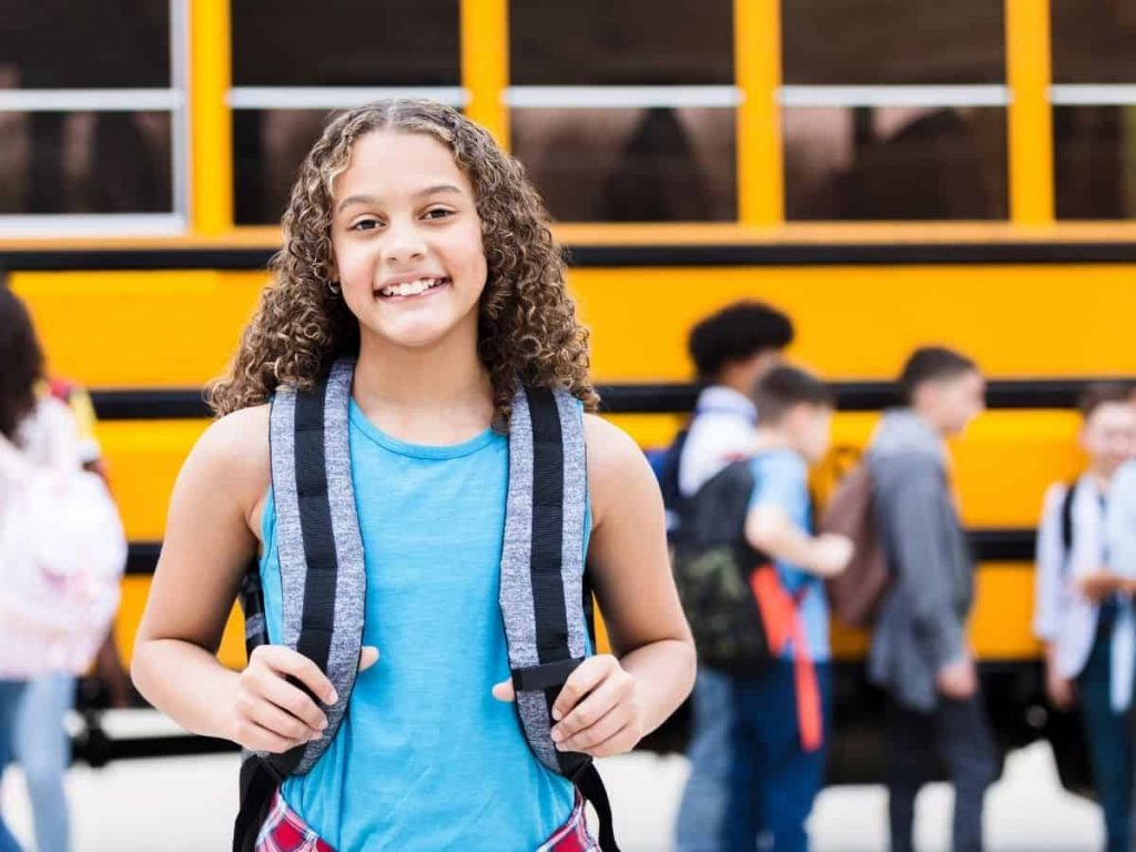 middle school girl smiling in front of a bus