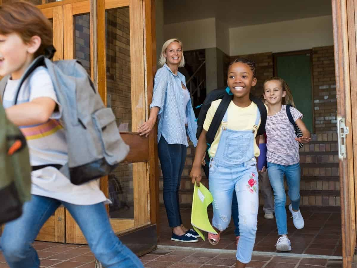 teacher holding door open for students running out